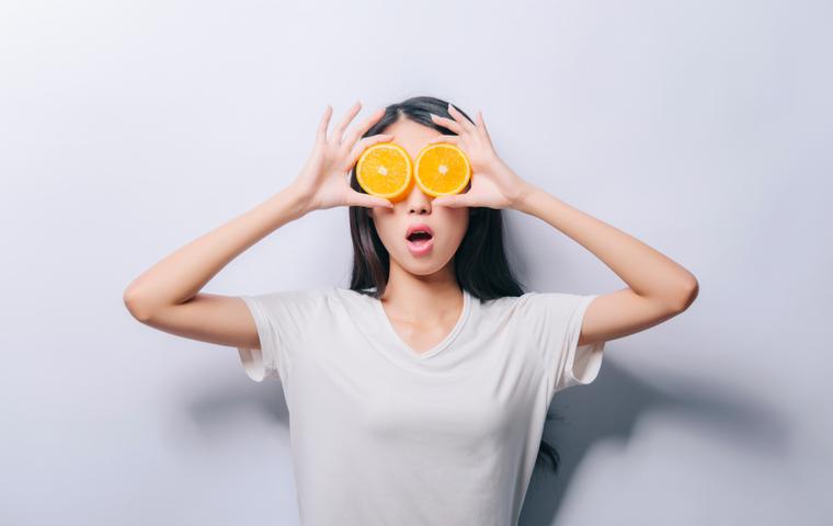 オレンジを手に持つ女性
