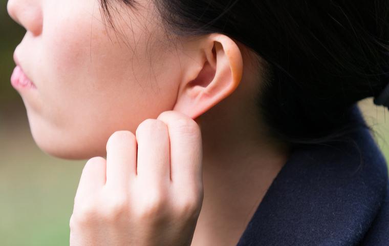 耳をつまむ女性